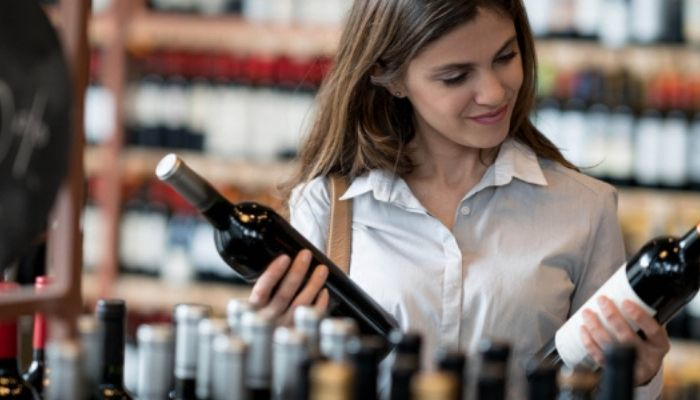 A buyer looking at wine bottles in the store
