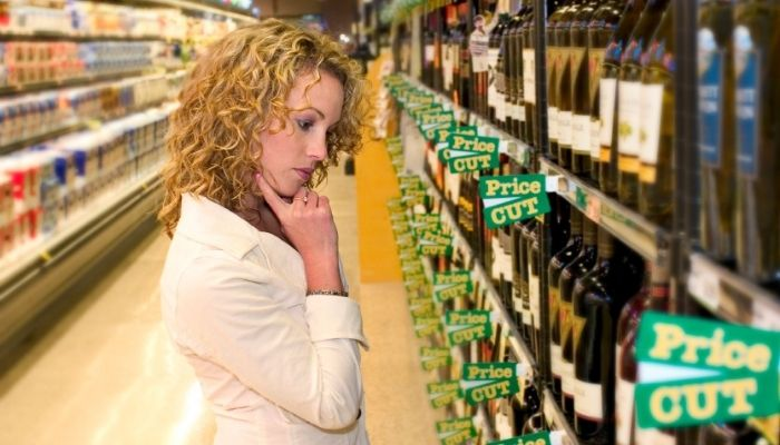shopper-looking-at-wine-bottles-in-store